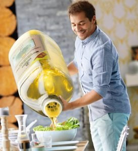 Guy pouring olive oil on the salad