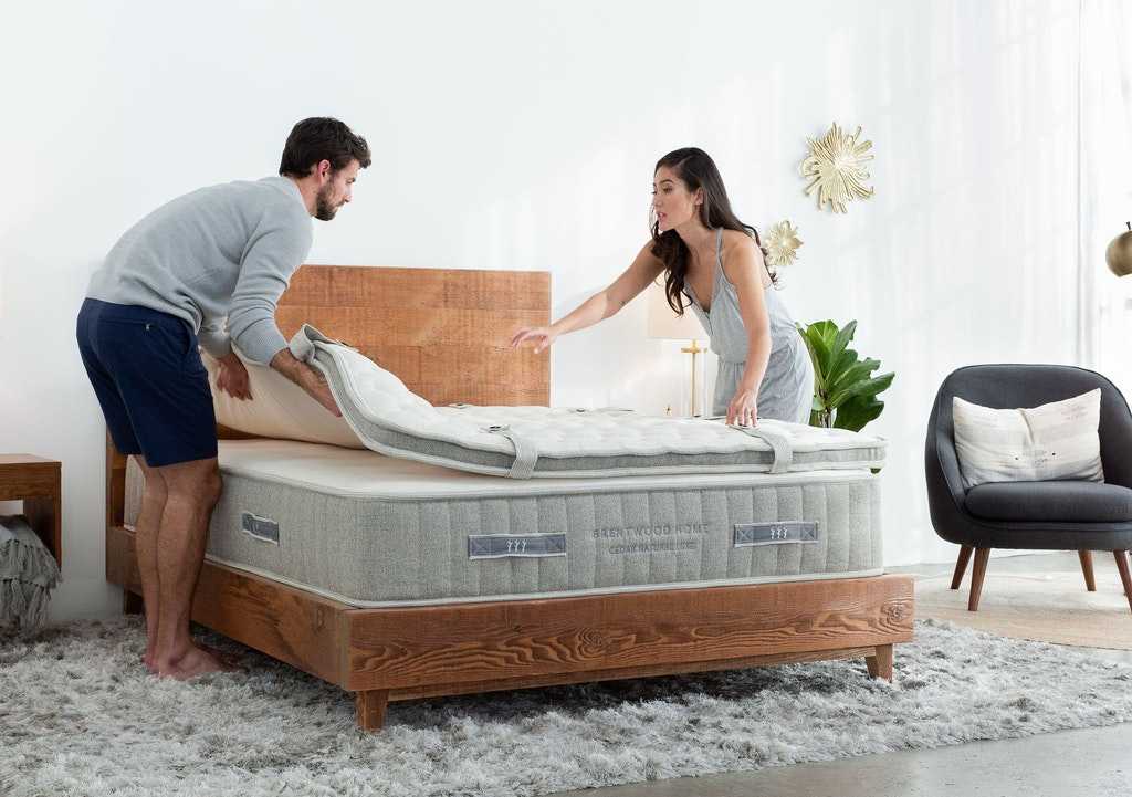 A couple is setting up the pillowtop portion of the Brentwood Home Cedar natural latex mattress.