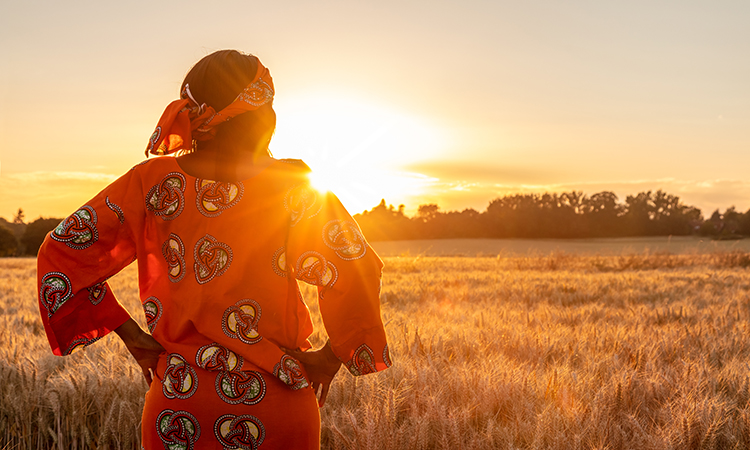 female farmer looking out over her farm in Africa