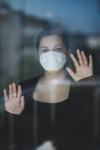 covid-anxiety woman with mask behind glass