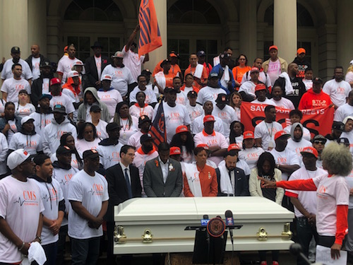 Advocates surround a casket representative of those who have been victims of gun violence. Photo Credit: RJ Sonbeek