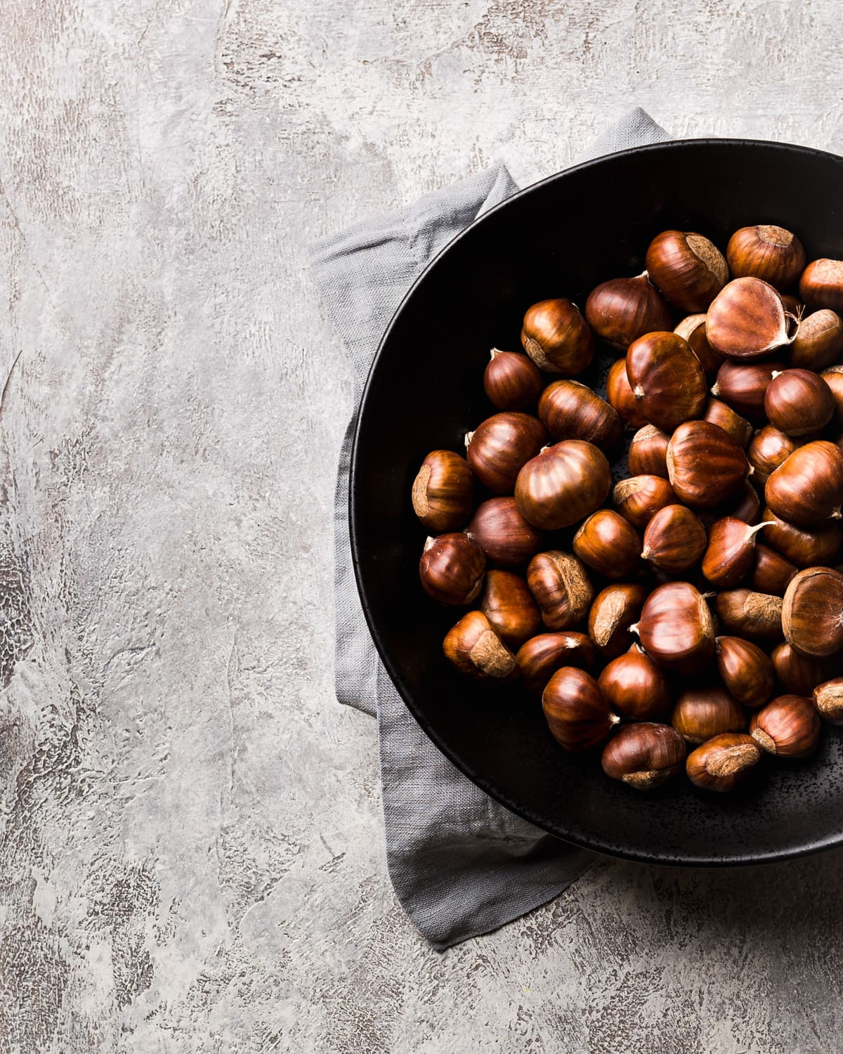 overhead shot of chestnuts in a black bowl with grey napkin