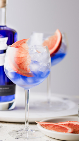 Emily Miller Food Photographer - wine glasses filled with blue gin, ice, and grapefruit slices