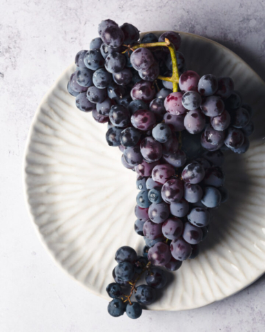 Overhead shot of Thomcord grapes on a white plate and concrete background