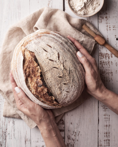 Emily Miller Food Photographer Hands holding sourdough loaf with bowl of flour and pastry brush