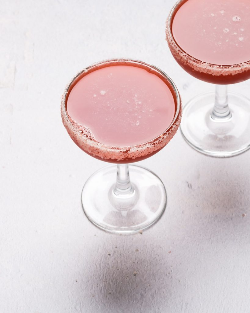 two coupe glasses filled with blood orange margaritas with salt on rim