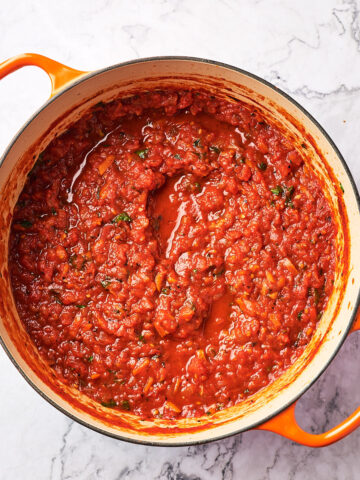 overhead of pot of vegan marinara sauce on marble background