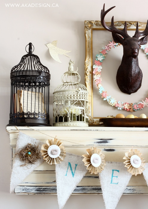 Spring Mantel with DIY floral paper wreath, burlap banner and bird cages.