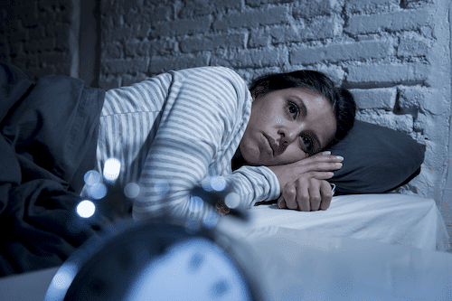 Woman lying in bed with insomnia, and could use help from a sleep coach for adults.