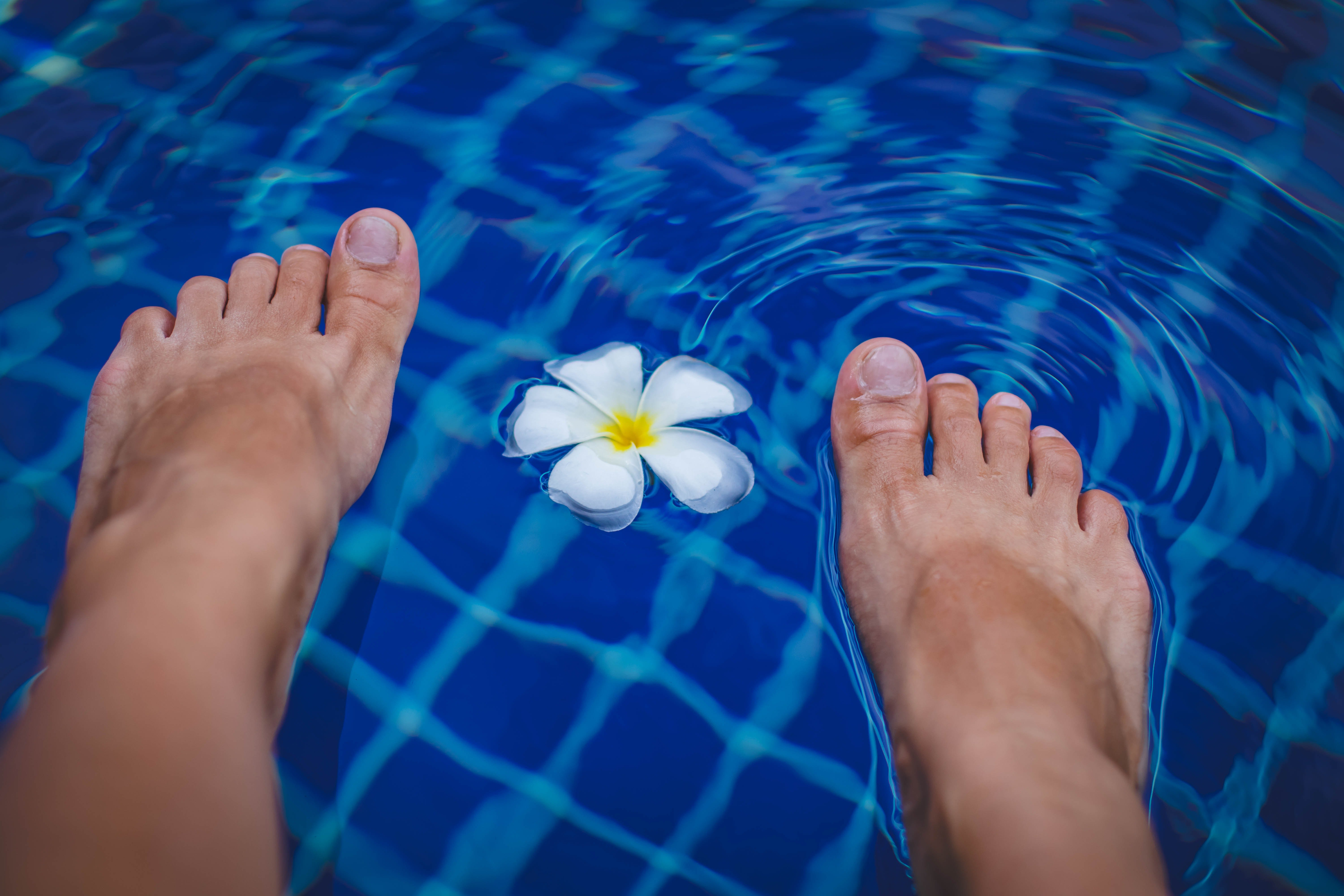 Image of feet and a flower floating on the top of clear pool with blue tile. Ionic detoxification foot bath services offered at the Karlfeldt Center of Idaho.