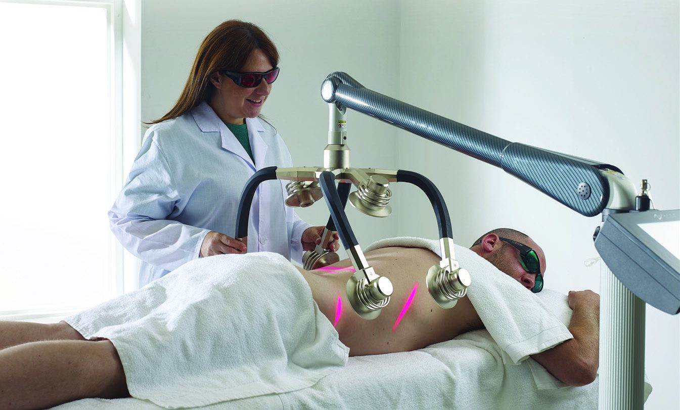 Zerona Laser - services provided by The Karlfeldt Center of Meridian, located just outside of Boise, Idaho. Image is a man lying prone receiving a treatment from a female technician in a white lab coat and sunglasses..