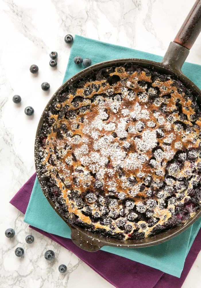 french blueberry clafoutis in a cast-iron skillet over two cloth napkins.