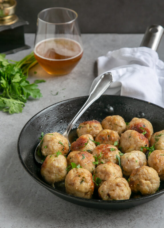 turkey meatballs in pan with spoon, white napkin that cover the pan handle, glass of beer next to the pan and bunch of fresh parsley.