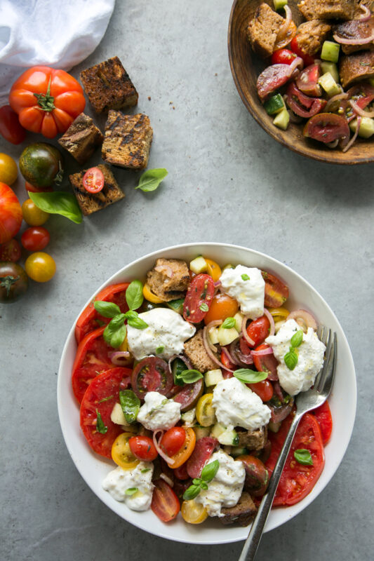 first recipe of 20-minute italian cookbook: burrata panzanella salad with a fork in a white place, tomatoes and grilled bread on the left side, small bowl with extra salad and bread on the right side