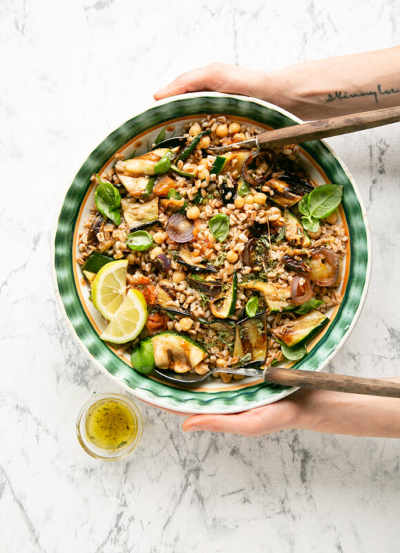 recipe from 20-minute italian cookbook: hands holding a bowl of farro salad with grilled vegetables, small pot of vinaigrette next to the salad