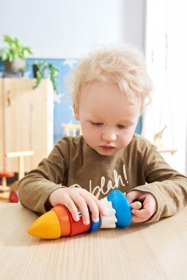 Kid playing with space rocket toy