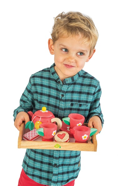 Boy holding red tea tray set by Tender Leaf Toys