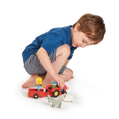 boy with wooden tractor and trailer toy by tender leaf toys