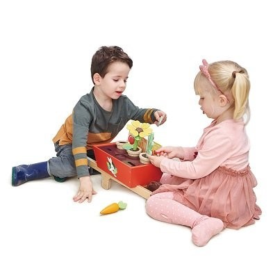 Kids playing together with garden set indoors