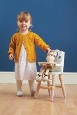 girl standing next to play chair
