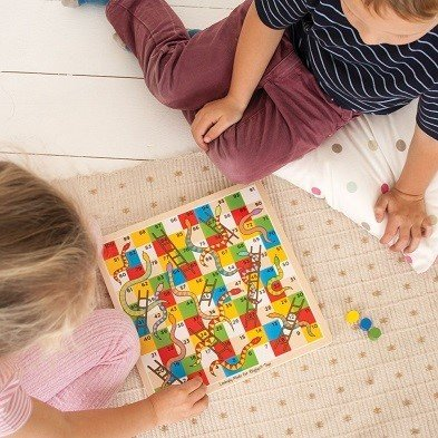 young players with traditional snakes and ladders family board game