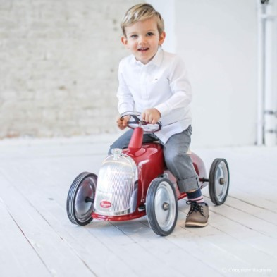 kid sitting on red toy car