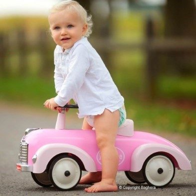 girl sitting on toy pink car