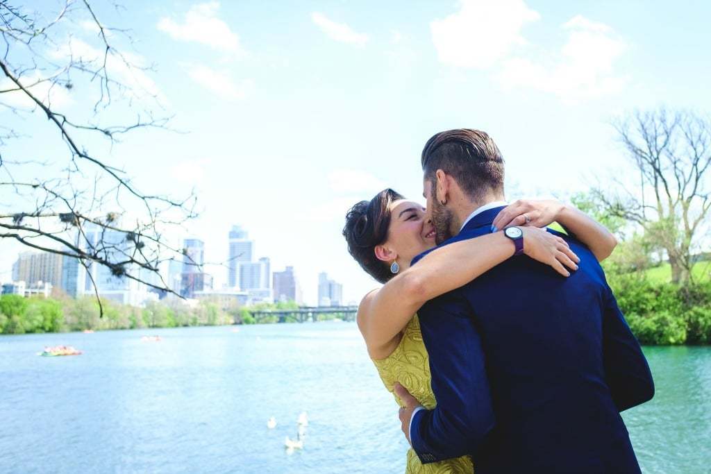 Bride in yellow dress, groom in navy suit kiss against Lady Bird Lake Austin backdrop