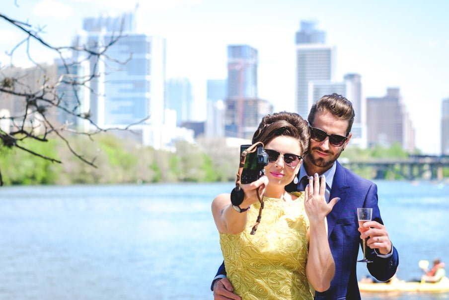 Bride in yellow dress, groom in navy suit, taking a selfie against Lady Bird Lake Austin backdrop
