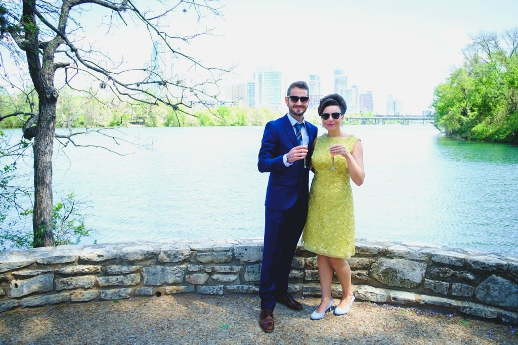 Bride in yellow dress, groom in navy suit, holding champagne flutes against Lady Bird Lake Austin backdrop