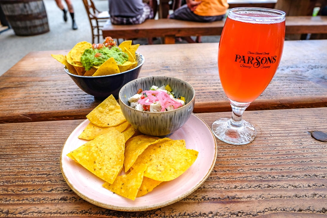 Dining in Prince Edward, nacho chips and dip with beer on table