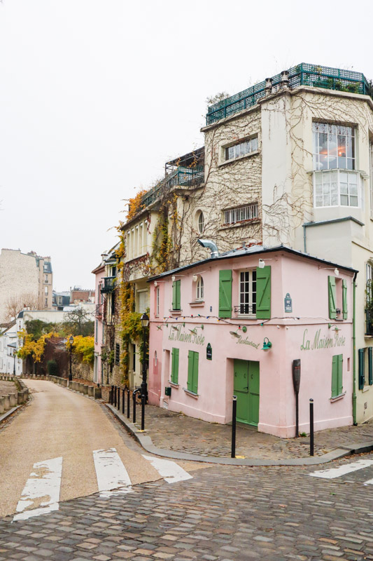 The famous restaurant, La Maison Rose in Paris. Pink building with green shutters and door at the corner of a Montmartre street.
