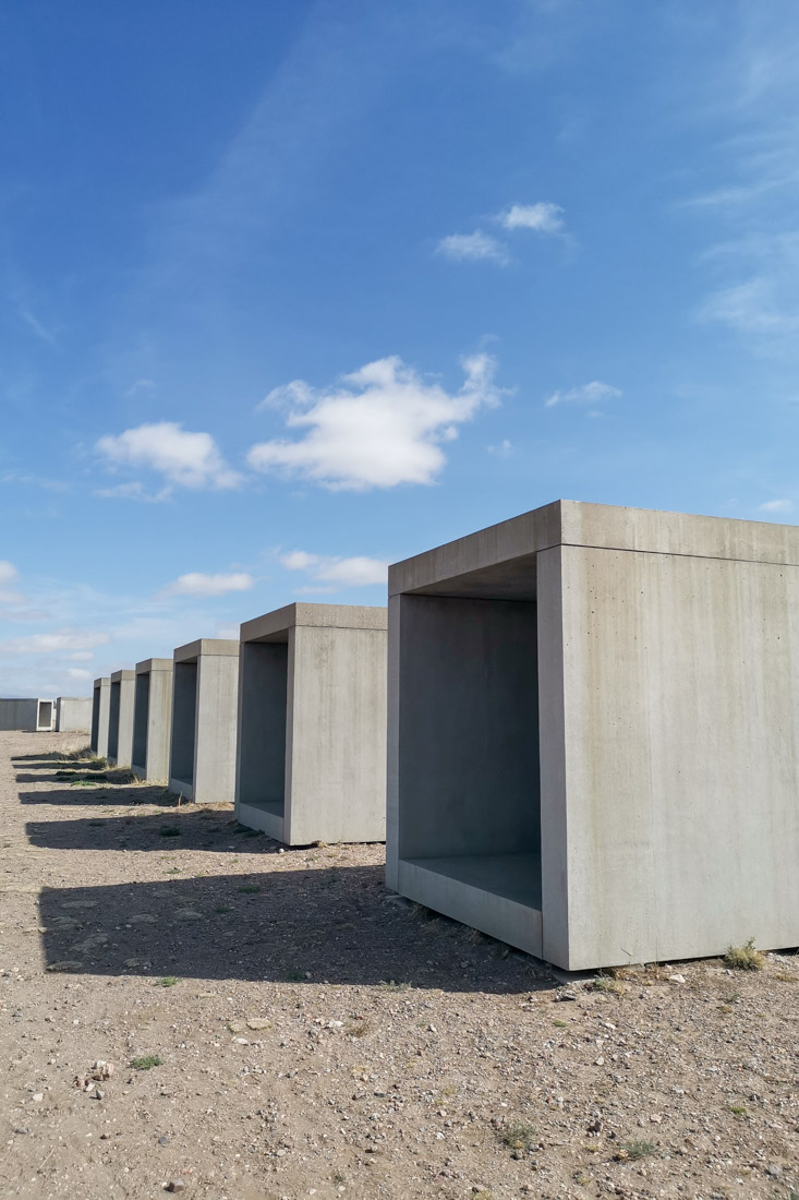 15 Untitled Works in Concrete in Marfa Texas Grey concrete hollow boxes on sandy ground with blue skies and shadows