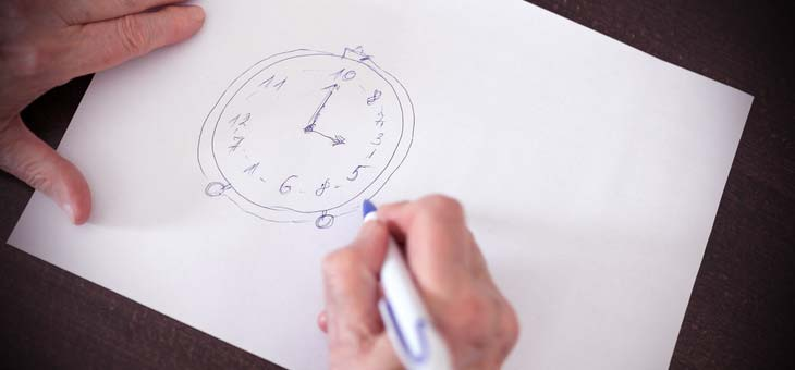 close up view of a senior womans hands drawing Alzheimers disease cognitive functions clock test