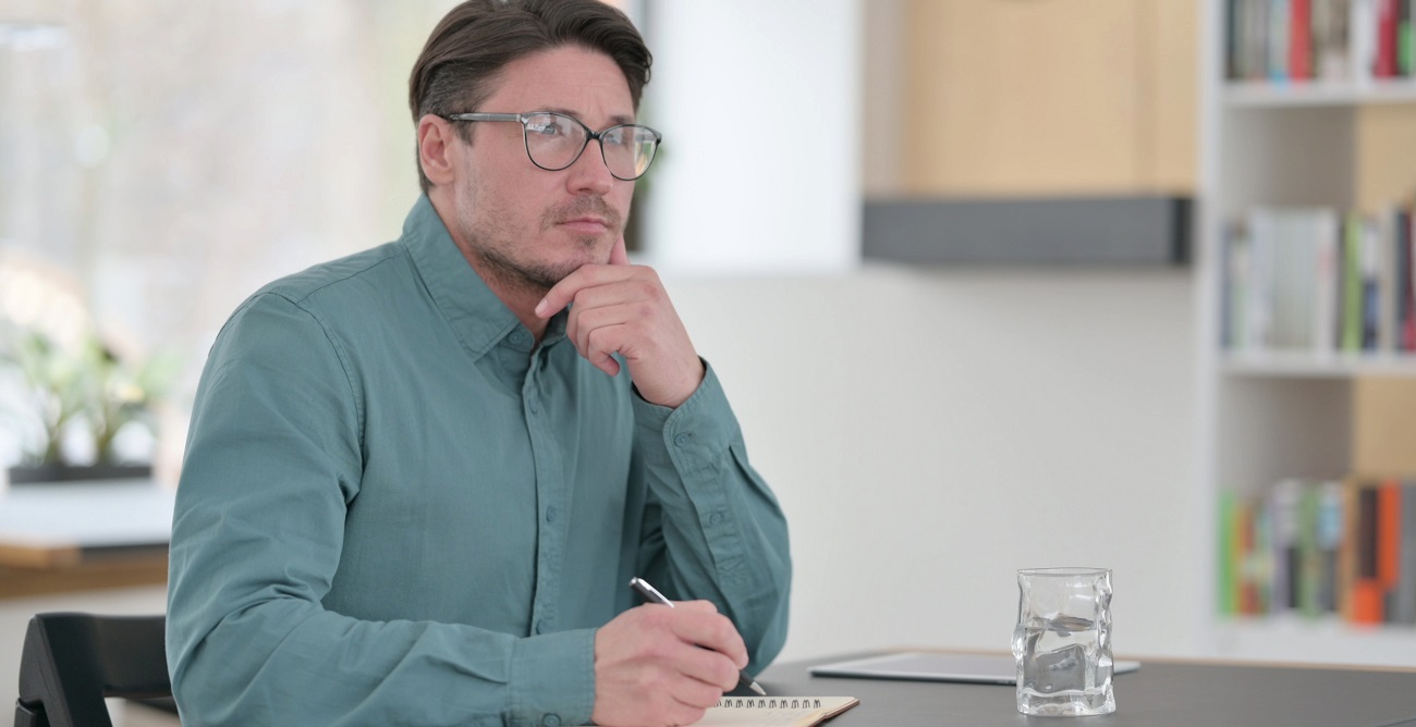 Middle aged man looks thoughtful as he considers canceling his health insurance