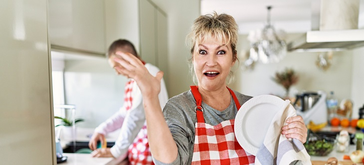 woman in kitchen in apron smiling