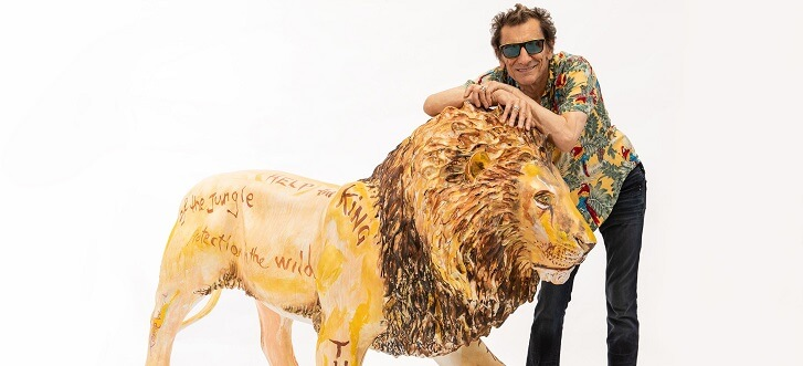 man leaning on sculpture of lion