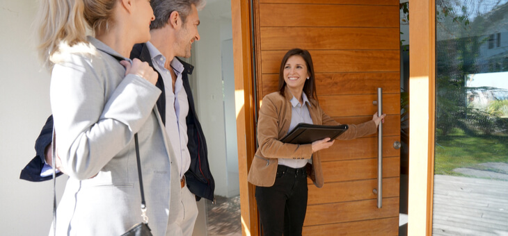 real estate agent showing couple into house