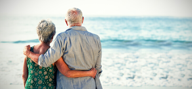 grey haired couple on beach looking at water