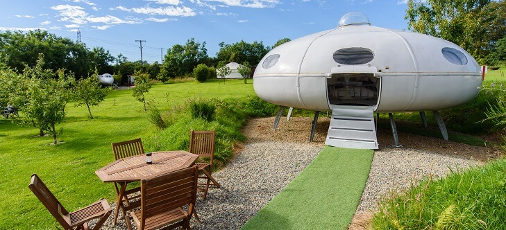 saucer shaped cabin in grassy field