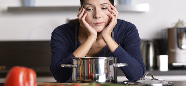 bored woman looking at food in kitchen