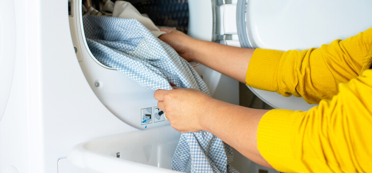 woman's hands putting clothes into tumble dryer