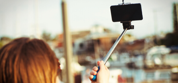girl with phone on selfie stick