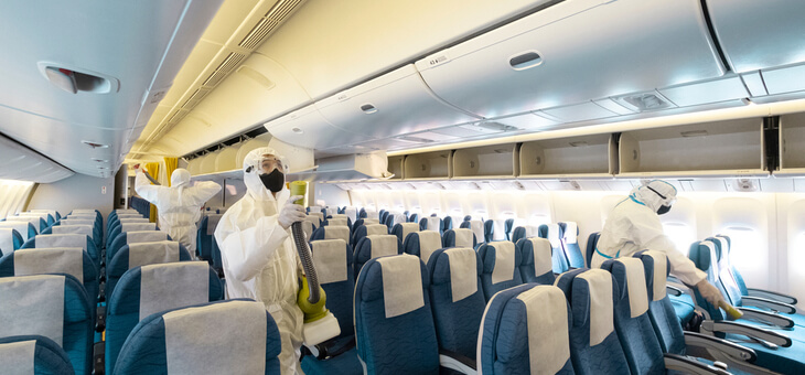 workers in protective gear sanitising empty plane