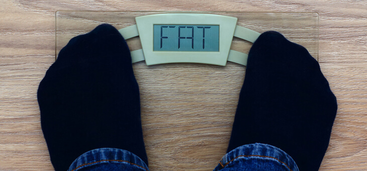 male feet standing on scale that reads fat