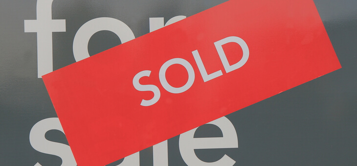 real estate for sale sign with sold sticker