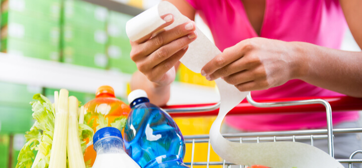 woman leaning on trolley full of shopping examining receipt