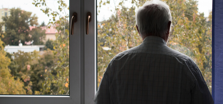 rear view lonely older man staring out window
