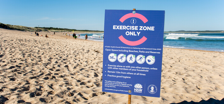 empty sydney beach with covid 19 restriction sign