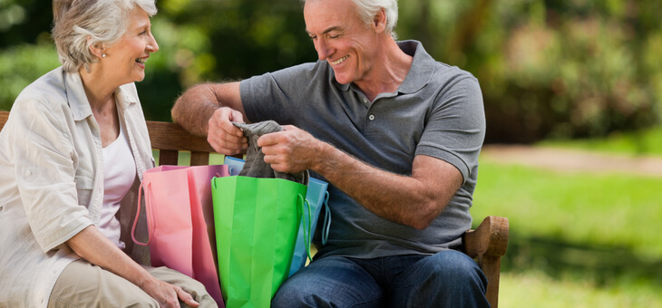 smiling older couple on park bench with shopping bags